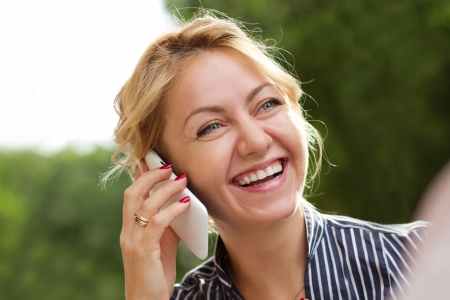 Young attractive businesswoman talking on the phone laughing photo