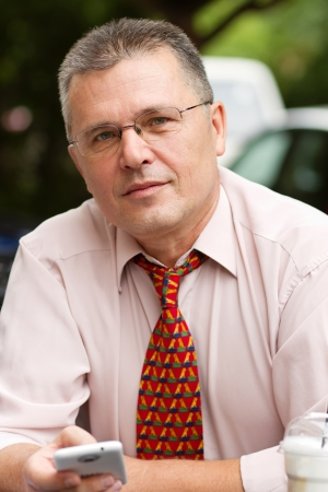 respectable: Portrait of respectable senior businessman holding a trendy smart phone