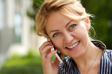 Young attractive businesswoman talking on the phone smiling photo