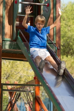 Little boy posing on the playgorund at bright summer day