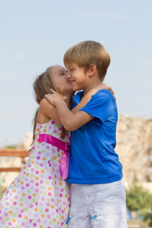 girls kissing: Cute little children on the playground at bright summer day