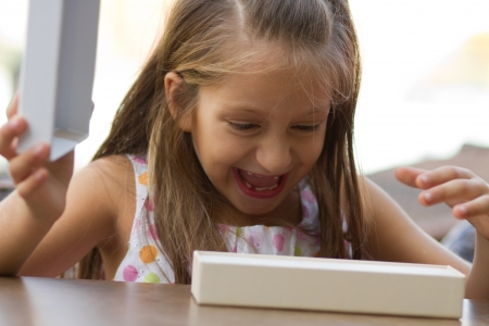 Little girls shows amazement opening the giftbox photo