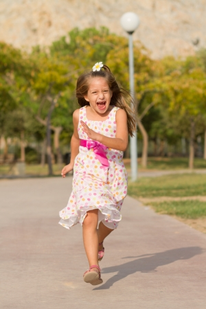 toothless: Cute little girl running in the park at bright summer day Stock Photo