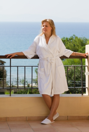 Attractive blond girl in white bathrobe relaxing after the bath at tourist resort photo