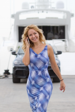 Wealthy young woman walks talking on the phone with expensive car and yacht on the background   photo