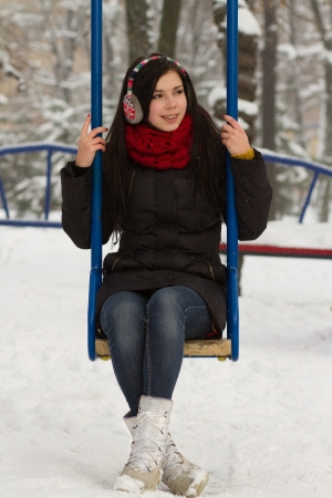 Pretty teenager girl on a walk outdoors at snowy winter day photo