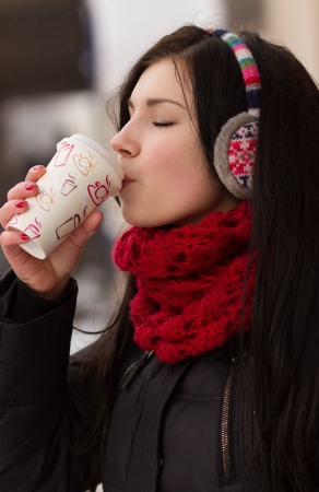 Teenager girl drinks hot coffee to warm up in winter