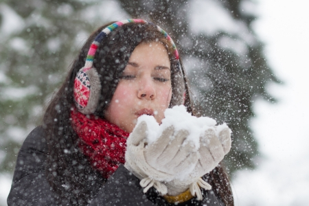 Teenager girl blowing fluffy snow form her hands in winter