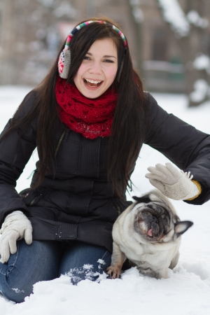 Young giel playing with funny pug puppy in snow photo
