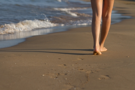 Feet of unrecognizable young woman walking on the sand photo