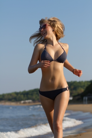Happy young blond girl enjoying her vacation on the beach of Mediterranean Sea in summer photo