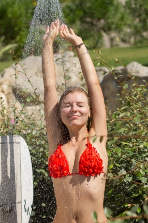 Sexy young blond girl in bikini having a shower outdoors in a bright summer day photo