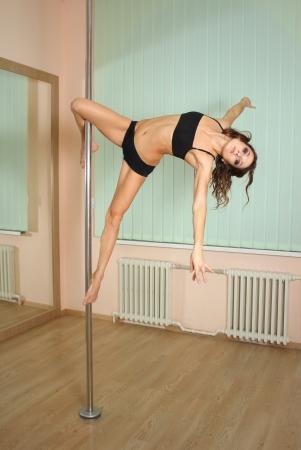 pole dancing: Jeune danseuse p�le professionnel exer�ant dans le studio de danse plastique bande