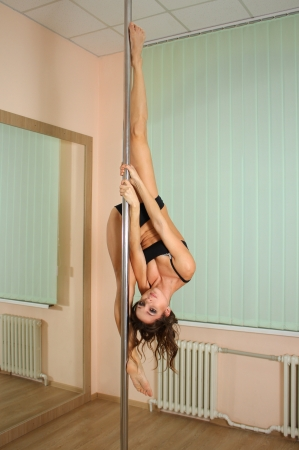 female stripper: Young professional pole dancer exercising in the studio in strip plastic dance