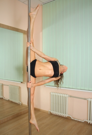stripper pole: Young professional pole dancer exercising in the studio in strip plastic dance