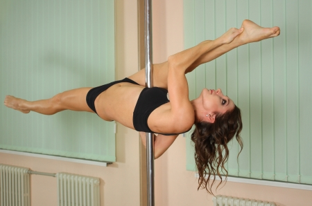 Young professional pole dancer exercising in the studio in strip plastic dance photo