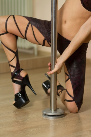 strip dance: Young professional pole dancer exercising in the studio in strip plastic dance