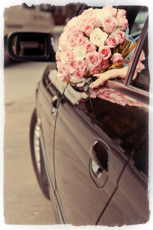 unrecognizable: Bride shows her beautiful wedding bouquet from window of a luxury car Stock Photo