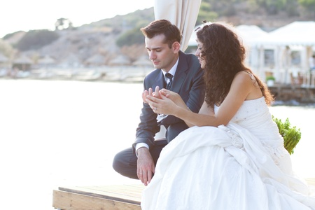 Happy newlyweds sitting at the water thinking about something intimate photo