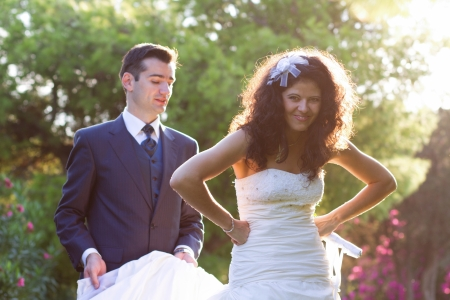Bride makes funny faces while her husband holds her dress photo