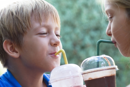 Little brother and sister drinking milkshakes in a cafe outdoors photo