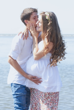 kissing pregnant belly: This young couple is happily waiting for their first child to be born  soon Stock Photo