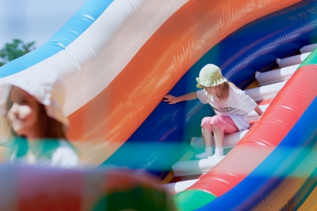 Young girls playing in a bouncing castle in a bright sunny day