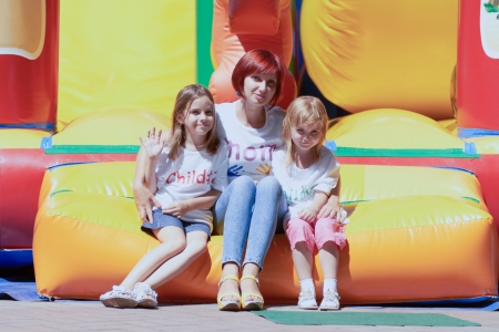 Young loving mother with her cute daughters sitting on the bouncing castle outdoors in a bright sunny day photo