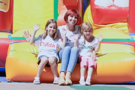 Young loving mother with her cute daughters having fun waving you on a bouncing castle outdoors in a bright sunny day photo