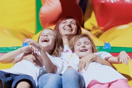 laughing out loud: Mam? y sus hijas por la que se re?a a carcajadas en un castillo hinchable en un brillante d?a de verano al aire libre Lovely day Foto de archivo