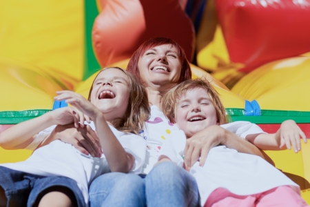 Mom and her daughters laughing out loud laying on a bouncing castle in a bright summer day outdoors Lovely day