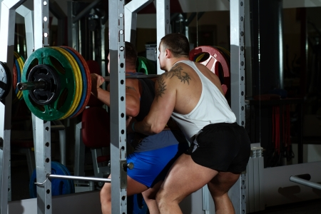 Pumped guys show how personal instructor  assists in crunching with heavy barbell photo