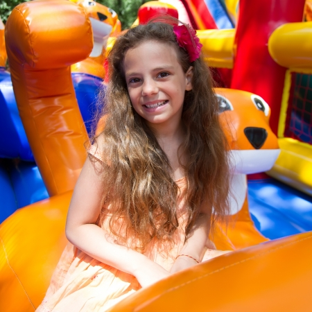 Cute little schoolgirl playing in bouncing castle outdoors at bright summer day photo