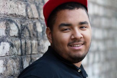 black block: Hombre negro joven que presenta en la pared de ladrillo gris en su bloque Foto de archivo