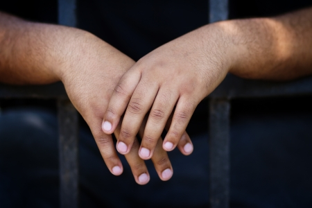 This photo is picturing hands of black prisoner in his chamber