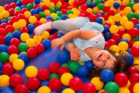 Kleine weiße Mädchen, die Spaß in der Hüpfburg am hellen Sommertag Standard-Bild - 21459875