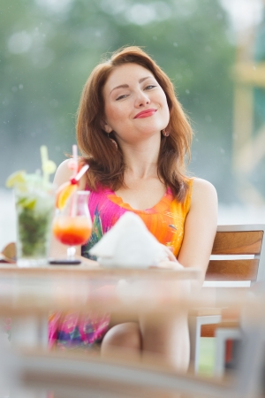 Beautiful young lady enjoying her fresh cocktail sitting in a restaurant outdoors photo