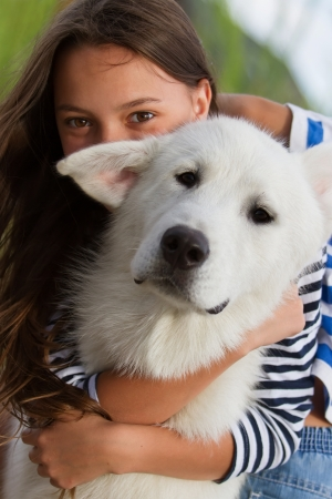 Portrait of a girl with her white alaskan malamute dog photo