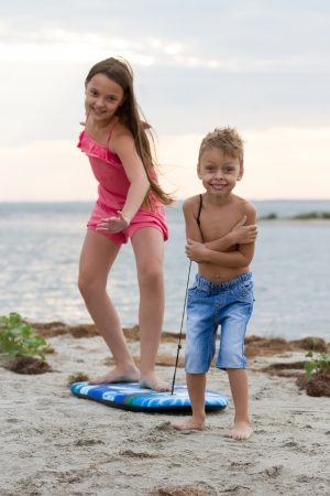 Happy little children playing with surfing board on the beach photo