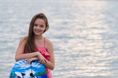 Pretty teen girl with her surfing board on the beach photo