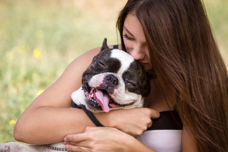hugging: Teenage brunette girl playing with her healthy young bulldog in the park Stock Photo