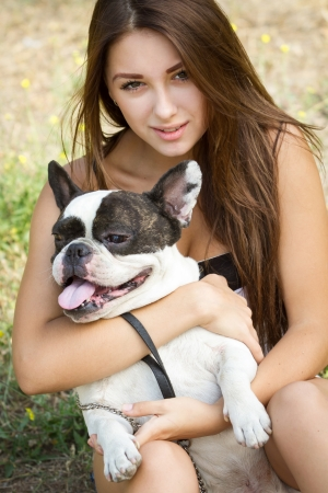 Teenage brunette girl playing with her healthy young bulldog in the park photo