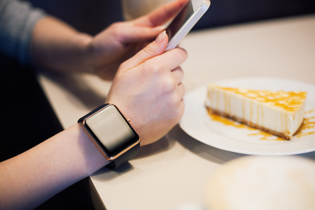 girl with a wristwatch: Girl taking photo of cheese cake with her smart phone while smart watch is on her hand. Focus on wristwatch, model unrecognizable.