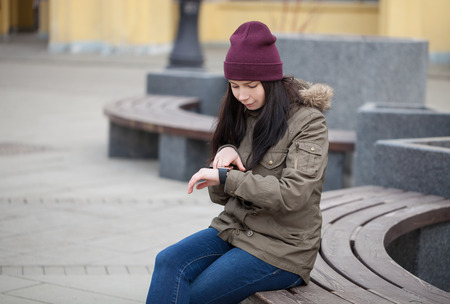 anywhere: Young girl in parka sitting on a bench using her smart watch. Stay connected to the social networks, internet and news from anywhere you want Stock Photo