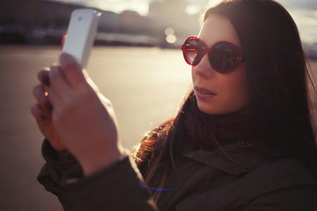 parka: Young hipster girl in grey parka coat and sunglasses taking photo with her trendy smart phone outdoors at bright spring day. Warm film color tones.