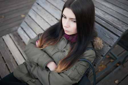 parka: Sad young hipster girl in grey parka coat sitting on a bench with serious expression. Not happy photo