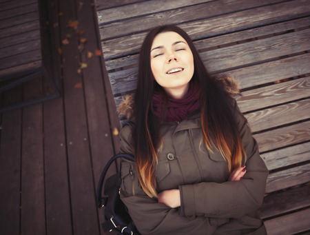 parka: Portrait of young hipster girl wearing grey parka coat and marsala scarf lying in calm on a bench. Good mood, happy facial expression