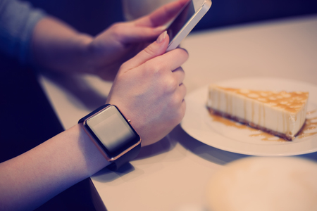 girl with a wristwatch: Girl taking photo of cheese cake with her smart phone while smart watch is on her hand. Focus on wristwatch, model unrecognizable, fading hipster colors used