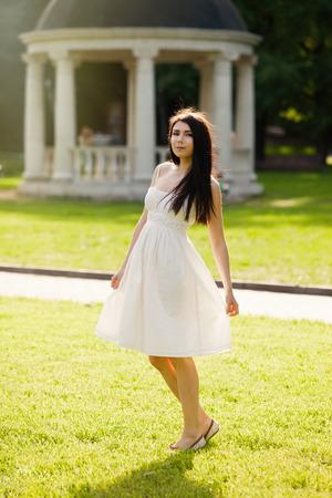 sundress: Young brunette girl in sundress posing at green park. Bright spring or summer day, warm season.