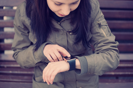 parka: Young girl in parka touching her smart watch on wrist. This new gadget lets you always stay connected to internet and social media networks from anywhere you want.